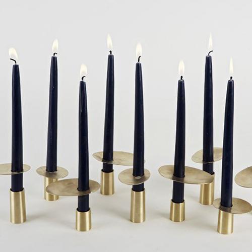 Zwarte kaarsen in metalen gouden kandelaars voor cosmopolitan luxury interieur